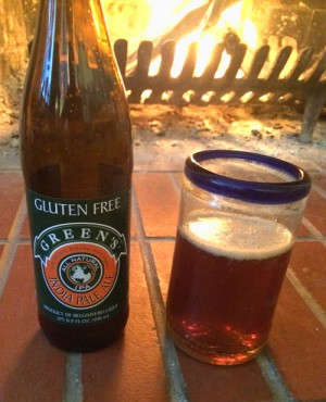 Bottle and Glass of Green's Gluten -free IPA for tasting, in front of a fireplace