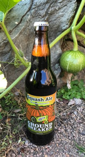 Ground Breaker Squash ale bottle in the garden with a squash